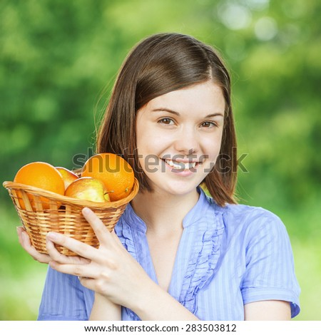 Portrait of young attractive dark-haired woman holding basket full of ripe juicy fruits at summer green park. - stock photo