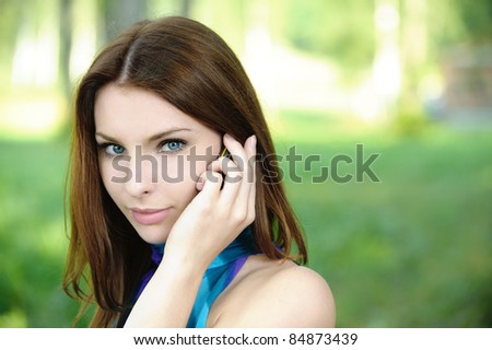 Portrait of young attractive dark-haired woman speaking on mobile phone at summer green park. - stock photo