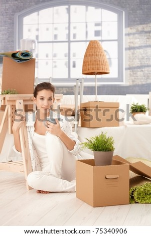 Portrait of young attractive female moving to new house, sitting on floor, drinking tea, boxes around.? - stock photo