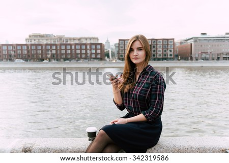 Portrait of young attractive female posing while chat on smart phone, gorgeous lady using cell telephone while rest outdoors, charming lady browsing internet on her cellular, copy space area for text - stock photo