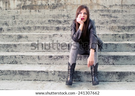 Portrait of young attractive girl in urban background - stock photo