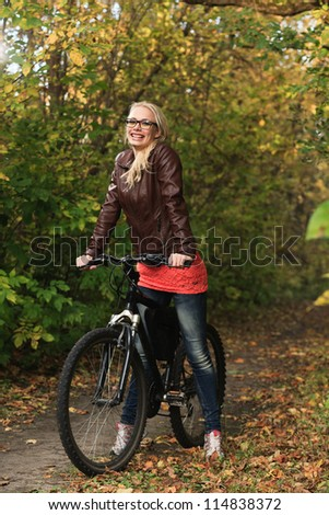 Portrait of young attractive girl on bicycle in the autumn forest