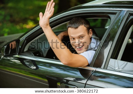 Portrait of young attractive handsome brunette man driving car and greeting somebody with hand. - stock photo