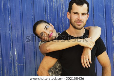 Portrait of young attractive heterosexual couple outdoor over grunge blue background. Beautiful woman embracing your boyfriend, image toned. - stock photo