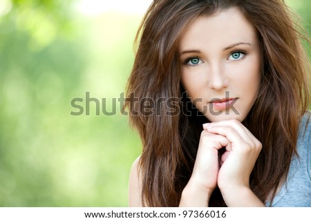 Portrait of young attractive long-haired woman propping up her face at summer green park - stock photo