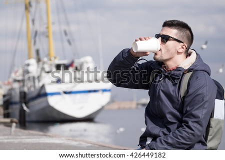 Portrait of young attractive man sitting on promenade and sight seeings as background - stock photo