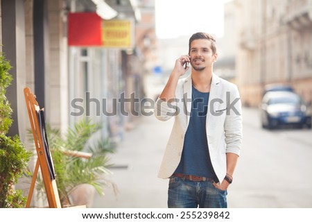 Portrait of young attractive man standing on the street and talking on the phone. - stock photo