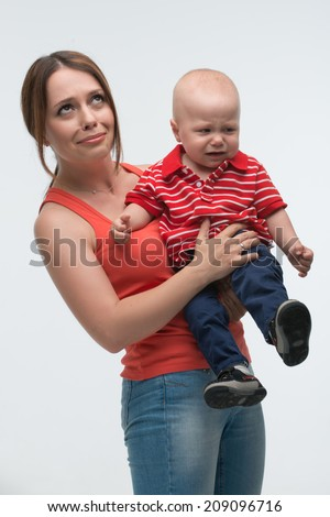 Portrait of young attractive mother holding her screaming toddler son being naughty and cranky, isolated on white - stock photo