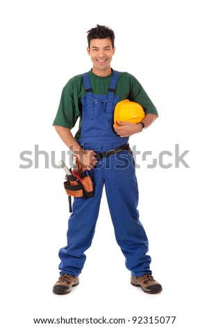 Portrait of young attractive Nepalese carpenter wearing a blue overall, tool belt and holding a  yellow helmet . Studio shot. White background. - stock photo