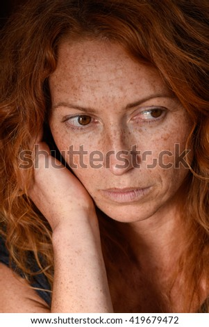portrait of young attractive red hair woman without makeup holding chin with hand thinking about emotional problems and looking away close up - stock photo