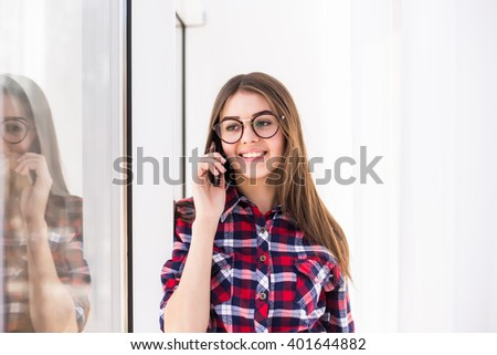 Portrait of young attractive smiling caucasian girl standing on background of window, talking per mobile phone. - stock photo