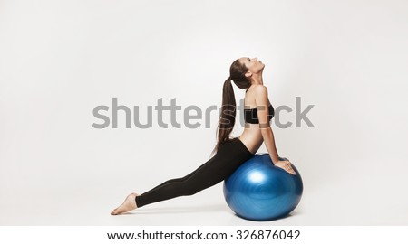 Portrait of young attractive woman doing exercises. Brunette with fit body holding fitness ball. Series of exercise poses. - stock photo