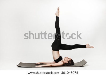 Portrait of young attractive woman doing exercises. Brunette with fit body on yoga mat. Healthy lifestyle and sports concept. Series of exercise poses. Isolated on white. - stock photo