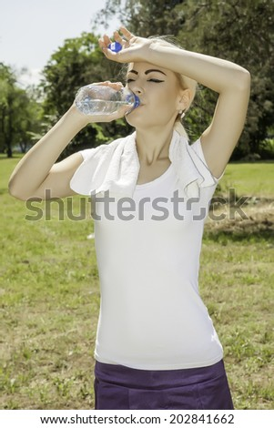 portrait of young attractive woman drinking water - stock photo