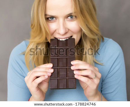portrait of young attractive woman eating chocolate - stock photo