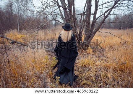 Portrait of young attractive woman in black coat and hat. She goes through the field. Autumn landscape, dry grass. Back view