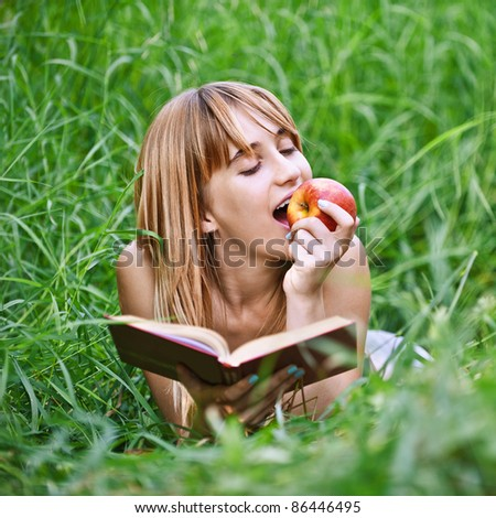 Portrait of young attractive woman lying in grass, reading book and eating apple at summer green park. - stock photo