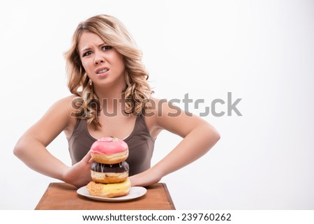 Portrait of young attractive woman sitting by the table rejecting doughnuts on the plate isolated on white background, diet concept - stock photo