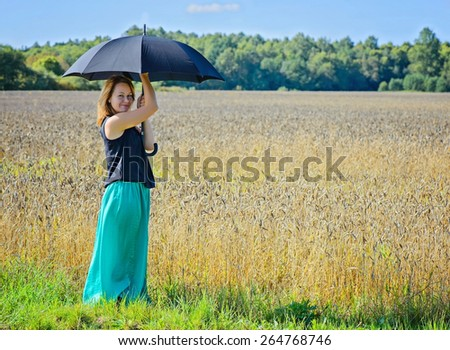 Portrait of young attractive woman with black umbrella in field under the blue sky - stock photo
