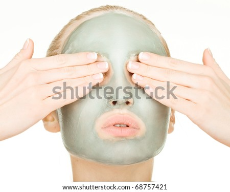 portrait of young attractive woman with cosmetic mask on her face - stock photo