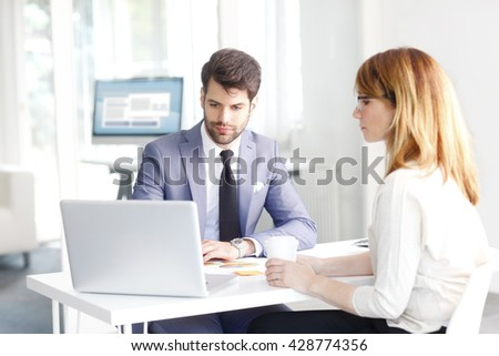 Portrait of young banking advisor sitting in front of laptop and helping a client with her banking accounts. - stock photo