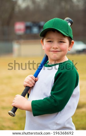 Portrait of young baseball player holding his bat in front of scoreboard - stock photo