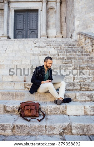 Portrait of young bearded man using his laptop while sitting on steps of city building