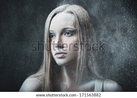Portrait of young, beautiful and emotional blonde woman over blowing wind and snowy blizzard - stock photo