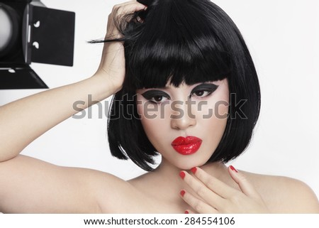 Portrait of young beautiful asian girl with thoughtful expression and photo flash on the background - stock photo