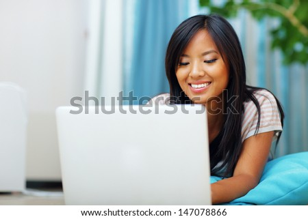 Portrait of young beautiful asian woman lying on the floor with laptop at home - stock photo