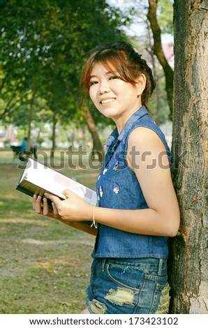 Portrait of young beautiful Asian woman reading a book in the garden under warm sunlight in the morning. - stock photo