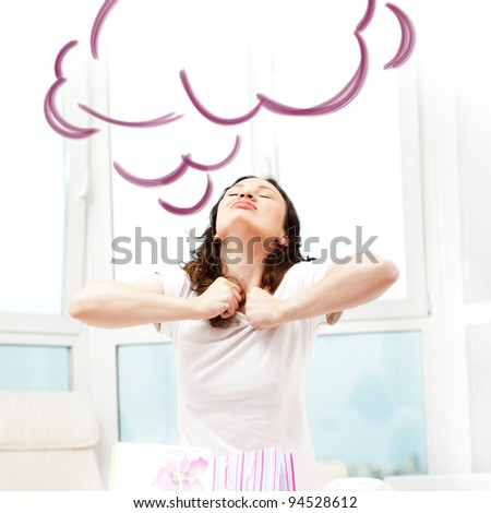 Portrait of young beautiful awake woman with gifts on bed at bedroom. She is happy and daydreaming. Blank cloud balloon overhead - stock photo