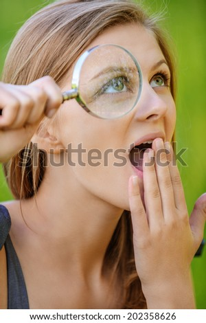 portrait of young beautiful blond amazed woman making invention with loupe