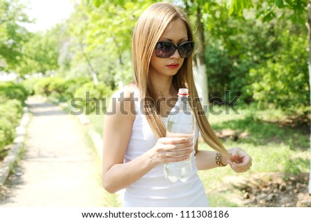 Portrait of young beautiful blond-haired woman wearing white t-shirt drinking water at summer green park. - stock photo