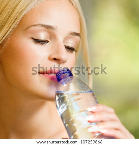 Portrait of young beautiful blond woman drinking water, outdoor - stock photo