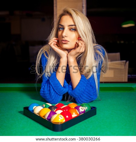 Portrait of young beautiful blonde girl with pyramid of pool balls. Billiard sport concept. Pool billiard game. American pool billiard. - stock photo