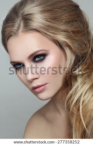 Portrait of young beautiful blonde girl with stylish messy hairdo and smoky eyes make-up - stock photo