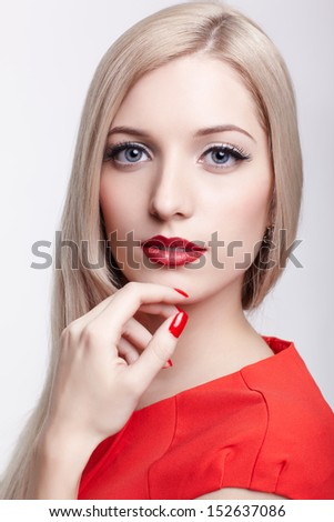 portrait of young beautiful blonde woman in red dress with red manicred fingers - stock photo
