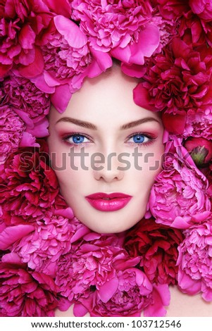 Portrait of young beautiful blue-eyed woman with pink peonies around her face - stock photo