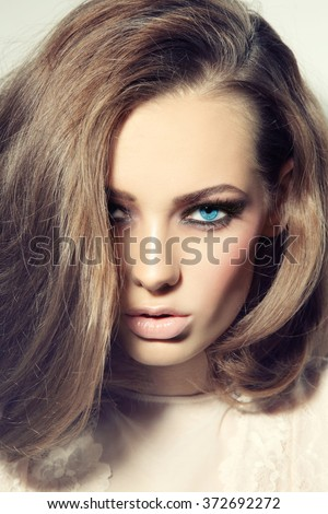 Portrait of young beautiful blue-eyed woman with stylish make-up and long hair