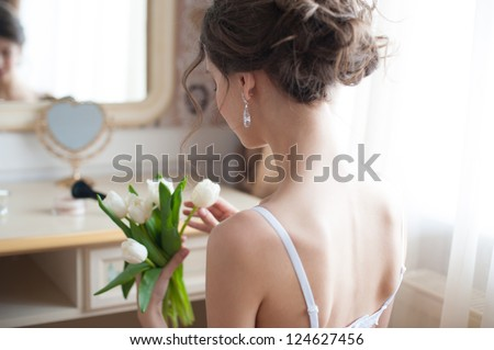 Portrait of young beautiful bride with bouquet of white tulips preparing to her wedding day - stock photo