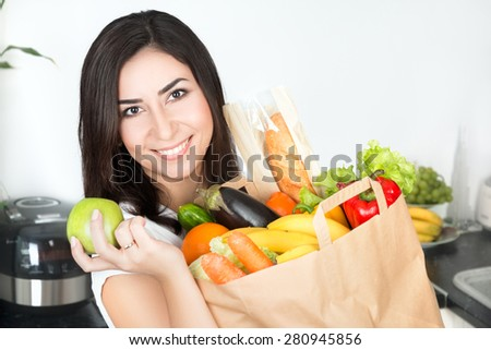 Portrait of young beautiful brunet woman standing on her kitchen with just delivered big paper bag full of vegetarian food and holding green apple - stock photo