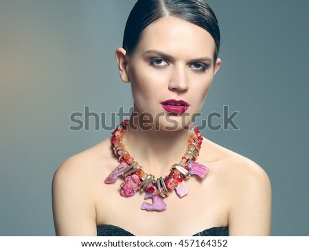 Portrait of young beautiful brunette woman in beads - stock photo