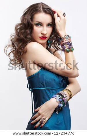 portrait of young beautiful brunette woman in blue dress and jewelery - stock photo