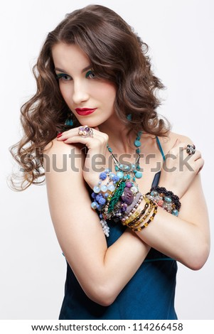 portrait of young beautiful brunette woman in blue dress and jewellery