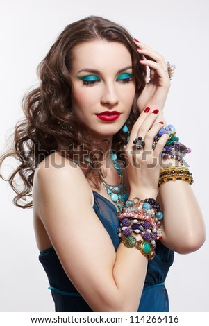 portrait of young beautiful brunette woman in blue dress, bracelets, ear-rings, beads and rings