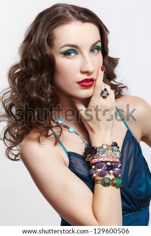 portrait of young beautiful brunette woman in blue dress, in beads, ear-rings, bracelets and rings