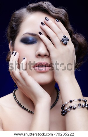portrait of young beautiful brunette woman in bracelet, necklace and ring with manicured fingers touching her face - stock photo