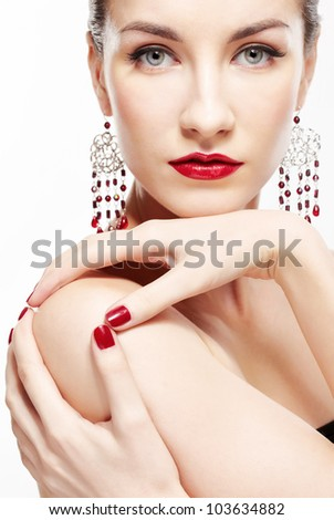 portrait of young beautiful brunette woman in ear-rings touching her shoulder with manicured fingers - stock photo
