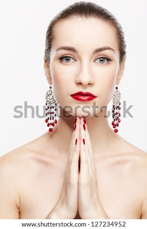 portrait of young beautiful brunette woman in jewelery posing on gray - stock photo